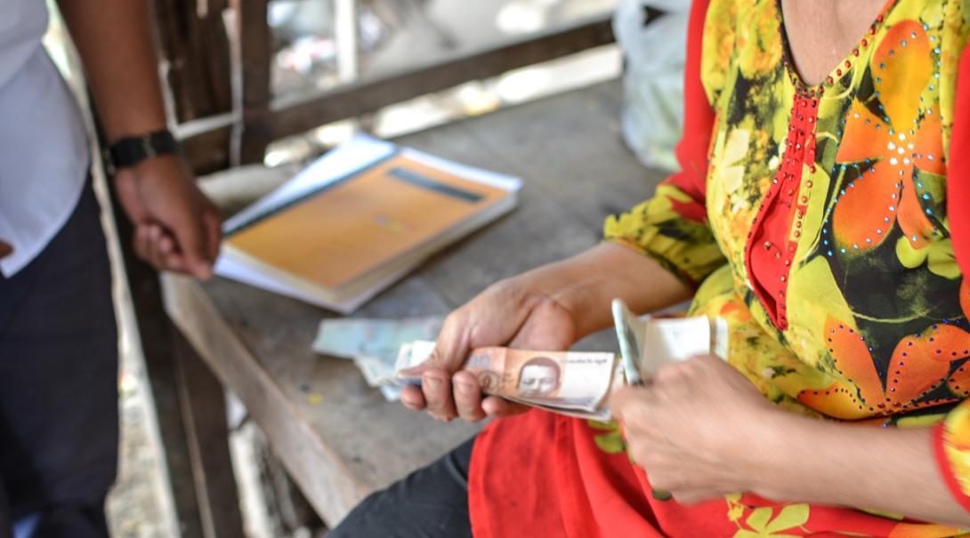 利益を確認するマイクロファイナンスインターンとカンボジアのローン受益者